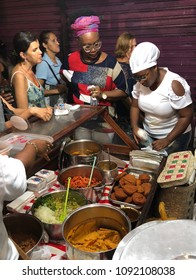 SALVADOR, BRAZIL - MARCH 02, 2018: Brazilian Baiana woman assembles a plate of traditional acaraje fritters from a stall on the street.