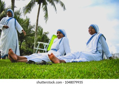 SALVADOR, BRAZIL -?? MAY 5, 2011: Three Catholic nuns from the order Missionaries of Charity relax on the grass in the summer while on an outing in Salvador, Brazil