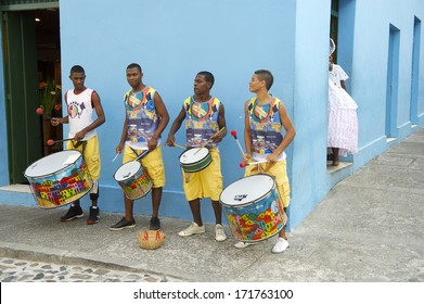 SALVADOR, BRAZIL - OCTOBER 15, 2013: Four unidentified young Brazilian men in colorful clothing stand drumming on a sidewalk in the historical center of Pelourinho, famous for its percussion bands.