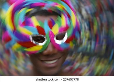 Salvador Carnival scene features samba dancing Brazilian man smiling in colorful mask in Pelourinho