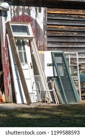 salvage doors and windows are for sale and lie against a rustic old wooden barn in Michigan USA