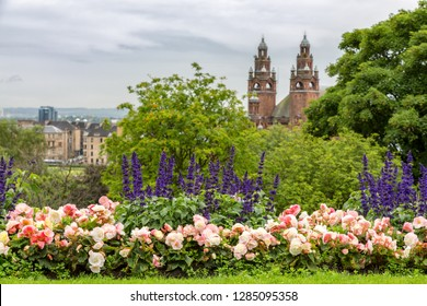 Salvia and begonia flowers in the flower beds or Kelvingrove park, Glasgow, Scotland, The Kelvingrove museum and the west end of the city can be seen in the distance.