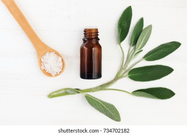 Salvia officinalis essential oil and sea salt for natural skincare, top view. Green fresh leaves, dropper bottle, holistic ingredients.