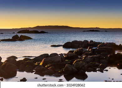 Salvora Island in Atlantic national park at dusk with coastal roks in foreground