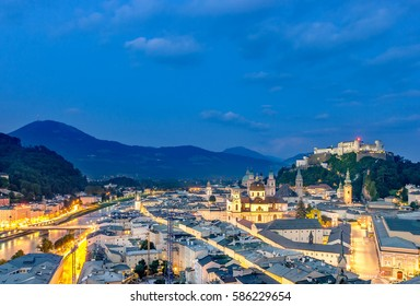 Salzburg, Aerial panoramic view of the famous historic city with Illuminated Festung Hohensalzburg Fortress, Cathedral and Salzach river in twilight during blue hour at dusk, Salzburger Land, Austria