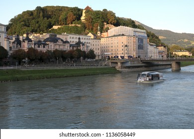 SALZBURG, AUSTRIA 15 AUG 2017: Cafe Bazar building on the left and boat cruising down Salzach river viewed at sunset