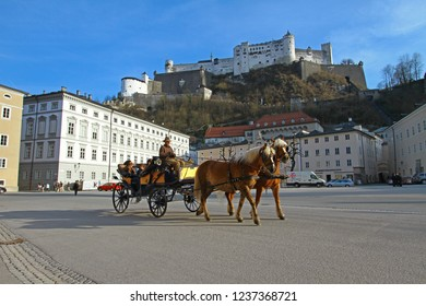 Salzburg, Austria - April 4, 2012: horse carriage with coachman and family as passengers go through beautiful city street with famous mighty Hohensalzburg Fortress at background on sunny spring day.