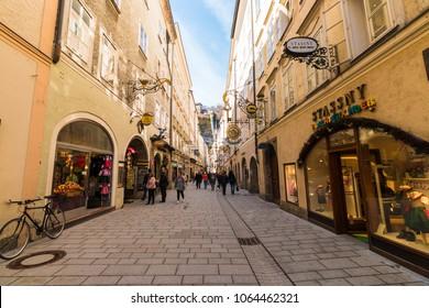 Salzburg, Austria - April 6, 2018: People strolling through Getreidegasse - famous shopping street in Salzburg old town.