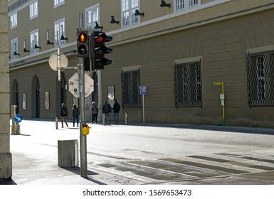 Salzburg, Austria - CIRCA OCTOBER 2019. Pedestrian stop and walk signal in Salzburg. Empty street and crosswalk in city.