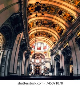 SALZBURG, AUSTRIA - FEBRUARY 19, 2016: Interiors of Baroque Cathedral of Roman Catholic church in Salzburg, Austria. Main altar from the nave. Illuminated ceiling with rows.