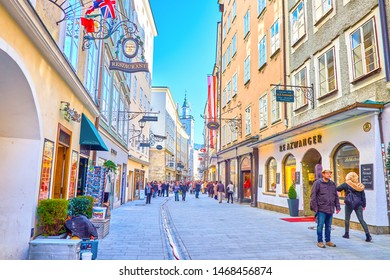 SALZBURG, AUSTRIA - FEBRUARY 27, 2019: Narrow and busy Getreidegasse shopping street with fashion boutiques, art galleries and clock tower of old City Hall on background, on February 27 in Salzburg.