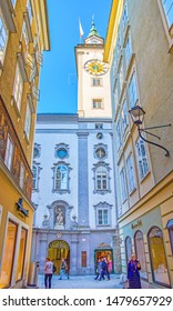 SALZBURG, AUSTRIA - FEBRUARY 27, 2019: The magnificent facade of Altes Rathaus (Old townhall) with high clock tower hidden in narrow medieval streets of Altstadt (old town), on February 27 in Salzburg
