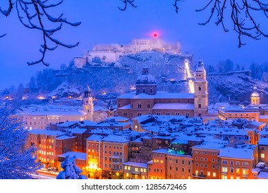 Salzburg, Austria: Heavy snow on the historic city of Salzburg with famous Festung Hohensalzburg and Salzach river illuminated in beautiful twilight during scenic Christmas time in winter