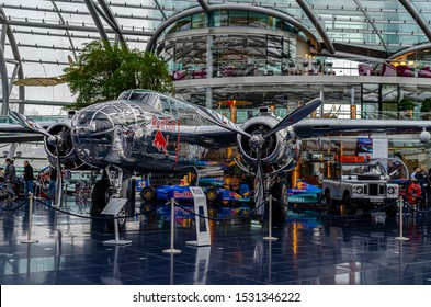 Salzburg / Austria January 19, 2019: North American B-25J Mitchell bomber airplane exhibited in Red Bull Hangar 7 Museum in Salzburg on the background of Red Bull Team cars.
