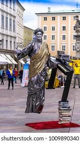 SALZBURG, AUSTRIA - JULY 15, 2017: Street artist-illusionist performing levitation trick in the old center of Salzburg, Austria