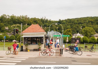 Salzburg, Austria - July 18, 2019: People walking and waiting for lights to change at the crossing with bicycles near Mozart bridge (Mozartsteg) in the old town. Salzburg street life.