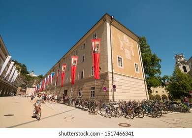 Salzburg, Austria - July 23, 2019: Young girl riding a bicycle along bike parking on Hofstallgasse, near University building and Salzburg festival flags in the old town.