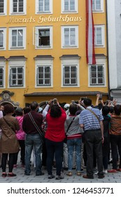 "SALZBURG, AUSTRIA - JUNE 2018: Tourists taking Foto in front of Mozart's Birthplace , Austria. Mozart lived on the third floor of the ""Hagenauer House"" at Getreidegasse 9 from 1747 to 1773"