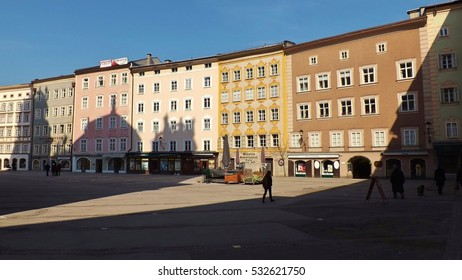 Salzburg, Austria - March 15, 2015: On the University square or Universitatsplatz in Salzburg. View of the Mozart birth house, amongst others. One can see the shadow of the collegiate church.