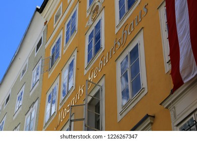 "Salzburg, Austria - May 20th 2014: Facade of Mozart's Birthplace in the Altstadt (Old Town) of Salzburg with the golden lettering ""Mozarts Geburtshaus"" and with clouds are reflecting in the windows"