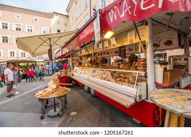 Salzburg, Austria - September 11, 2018: Gastronomy market wagon with cheese, sausages and other local austrian delicacies on the market at Universitatsplatz in the heart of the old town of Salzburg.
