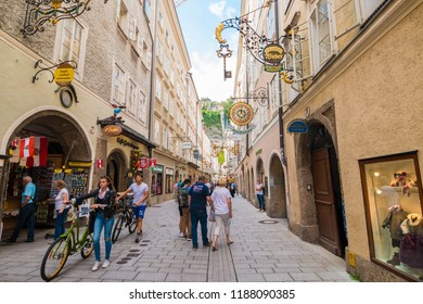 Salzburg, Austria - September 13, 2018: Famous busy pedestrian shopping  street Getreidegasse with vintage  wrought iron guild signs in the old town of Salzburg.