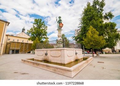 Salzburg, Austria - September 13, 2018: Wild man fountain (Wilder Mann Brunnen) on Max Reinhardt Platz square in the old town. The statue dates back to 1620 and is holding coat of arms of Salzburg.