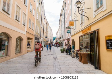 Salzburg, Austria - September 13, 2018: People walking and riding bicycle on Linzergasse - popular pedestrian shopping street on the right side of Salzach river.