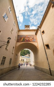 "Salzburg, Austria - September 13, 2018: A small street  Franziskanergasse in the old town of Salzburg. A fresco""The Lamentation of Christ""  by salzburger artist Georg Jung seen above the arch."