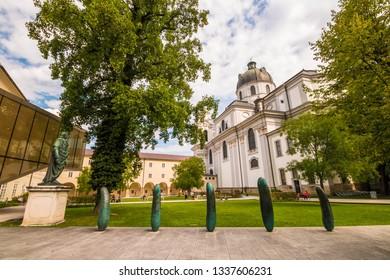 Salzburg, Austria - September 13, 2018: Small park Furtwaenglerpark with green lawn near University of Salzburg and  baroque Kollegienkirche (Collegiate Church) in the old town.