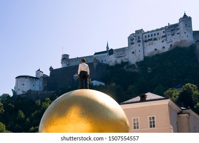 "Salzburg, Austria - September 15, 2019: View of the sculpture of the man on a golden ball (modern art work ""Sphaera"") on the Chapter Square (German: Kapitelplatz) of the historical old town."