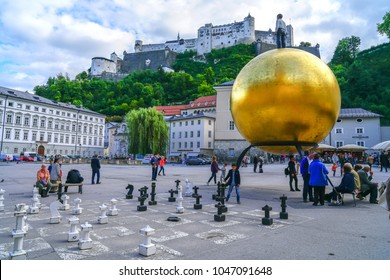 SALZBURG AUSTRIA - SEPTEMBER 6 ; Large golden sphere sculpture in Capital Square, outdoor chess board and pieces people relaxing and wandering through September 6 2017 Salzburg Austria
