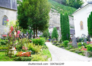 SALZBURG, AUSTRIA - SEPTEMBER 6; Tourists on path between luxuriant cemetery gardens and graves and St. Peter's church  September 6 2017 Salzburg Austria