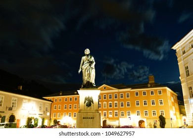 SALZBURG AUSTRIA - SEPTEMBER 7; Statue commemorating Mozart in Square at night illuminated and golden in color in Old Town September 7 2017 Salzburg Austria