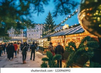 Mercado navideño de Salzburgo visto a través de las ramas de los árboles de Navidad