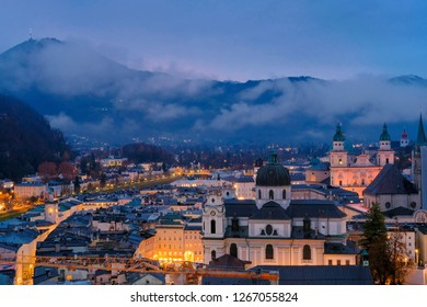 Salzburg morning cityscape with main Cathedral, Kollegienkirche and illuminated streets of old town on background of mountains in clouds