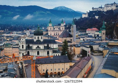 Salzburg morning cityscape with main Cathedral, Kollegienkirche and castle fortress Hohensalzburg on background of mountains in clouds