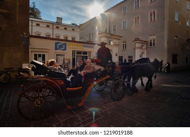 Salzburg, Salzburger Land, Austria - September 11, 2018: view of the historic city of Salzburg with traditonal horse-drawn Fiaker carriage on a sunny day with blue sky and bright sun light in summer.