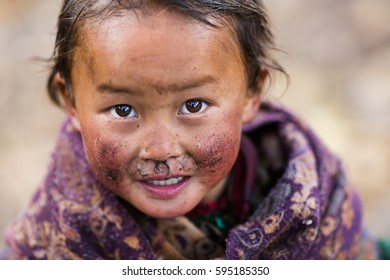 SAMAGAUN, NEPAL - OCTOBER 29, 2015:  An unidetified Tibetian child with a dirt on its face stares at the camera.