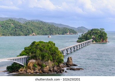 SAMANA - DOMINICAN REPUBLIC. Samana bridge. Beautiful separate standing rocky islands connects with the promenade bridge. Green hills with palmtrees on the background.