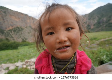 Samar, Upper Mutang / Nepal - August 22, 2014: Portrait of an unidentified little sick Tibetan girl with nasal discharge, amid the Himalayan mountains.
