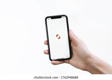 Samara Russia - 04.05.2020: A young man holds in his hand an iPhone 11 with the Shutterstock open application for contributors on a white isolated background