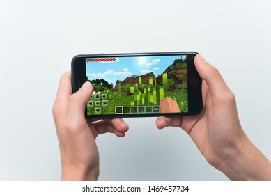 Samara, Russia -07, 29, 2019: A young guy playing minecraft game on Iphone 8 Plus. Teenage boy holding a phone in his hands with a game minecraft on a white background.