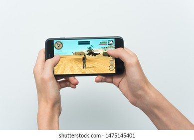 Samara, Russia -07, 29, 2019: A young guy playing GTA game on Iphone 8 Plus. Teenage boy holding a phone in his hands with a game Grand Theft Auto: San Andreas on a white background.