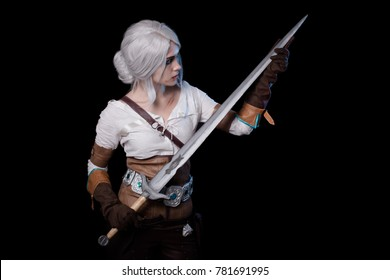 SAMARA, RUSSIA. 6 November 2016. Cosiri Ciri, the computer game and the book The Witcher 3: Wild Hunt. Beautiful woman warrior, check the sharpness of the blade, sharpen the sword. Black background.