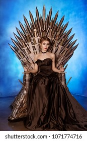 Samara, Russia - April 16, 2018. Studio photo session. A beautiful woman in a chic, black, evening dress sits on an iron throne of swords. Game of Thrones.
