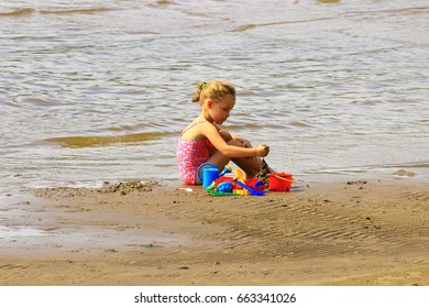 Samara, Russia - August 04, 2016. little girl sitting on the sand beach near the water, and enjoys playing with sand