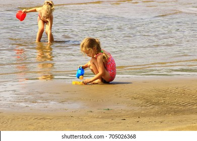Samara, Russia - August 04, 2016. two toddlers playing on a sandbank on the beach in summer a large river