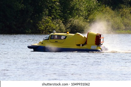 Samara, Russia - August 26/2017: a yellow hovercraft turns on the river on a sunny day, releasing water splashes