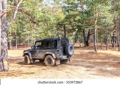 SAMARA, RUSSIA - CIRCA 2016: Land Rover Defender participates in fall offroad trip on the track across the forest. Land Rover Defender is a legendary offroad vehicle with over 68 years history.